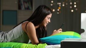 Tonårig flicka som hemma smsar i en smart telefon på en säng