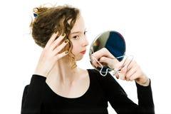 Tonårig flicka som kontrollerar blick i spegel hennes lockiga blonda hår - för att vara perfekt arkivbilder