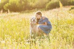 Tonårig flicka som kramar hennes golden retriever Arkivfoton