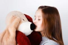 Tonårig flicka som kysser en leksakhund Royaltyfri Bild