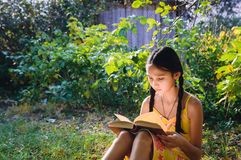 Tonårig flicka som läser en bok i trädgården royaltyfria bilder