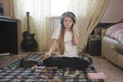 Tonårig flicka som lyssnar till musik i hörlurar som hemma sitter på golvet Fotografering för Bildbyråer