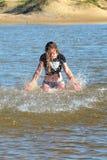 Tonårig flicka som plaskar i vatten fotografering för bildbyråer