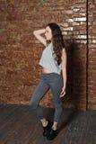 tonårig flicka som poserar nära en tegelstenvägg i källaren Royaltyfria Bilder