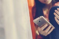 Tonårig flicka som rymmer en mobiltelefon som tonar instagram Livsstilstil fotografering för bildbyråer