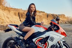 Tonårig flicka som sitter på en tävlings- motorcykel, härlig sexig cyklist i en kort kjol på en sportmotorcykel i natur En vän av royaltyfria bilder