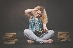 Tonårig flicka som sitter på golvet bredvid böcker och visar känslomässigt hennes hat, hat och trötthet fotografering för bildbyråer