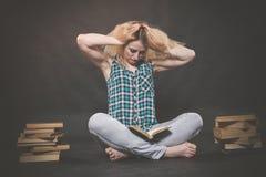 Tonårig flicka som sitter på golvet bredvid böcker och visar känslomässigt hennes hat, hat och trötthet arkivbild