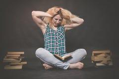 Tonårig flicka som sitter på golvet bredvid böcker och visar känslomässigt hennes hat, hat och trötthet royaltyfria bilder