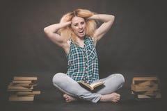 Tonårig flicka som sitter på golvet bredvid böcker och visar känslomässigt hennes hat, hat och trötthet royaltyfri bild