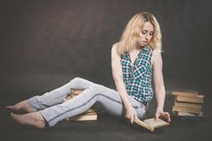 Tonårig flicka som sitter på golvet bredvid böcker och visar känslomässigt hennes hat, hat och trötthet royaltyfri fotografi