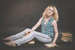 Tonårig flicka som sitter på golvet bredvid böcker och visar känslomässigt hennes hat, hat och trötthet royaltyfria foton