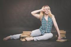 Tonårig flicka som sitter på golvet bredvid böcker och visar känslomässigt hennes hat, hat och trötthet arkivfoto