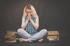 Tonårig flicka som sitter på golvet bredvid böcker och visar känslomässigt hennes hat, hat och trötthet arkivbilder