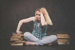 Tonårig flicka som sitter på golvet bredvid böcker och visar känslomässigt hennes hat, hat och trötthet arkivfoton