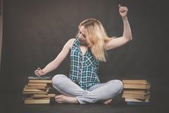 Tonårig flicka som sitter på golvet bredvid böcker och visar känslomässigt hennes hat, hat och trötthet royaltyfri foto