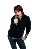 Tonårig flicka som sjunger med en mikrofon Arkivfoton