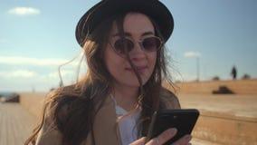 Tonårig flicka som smsar med vänner på smartphonen arkivfilmer