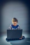 Tonårig flicka som spelar golvet i anteckningsbok på en grå färg Fotografering för Bildbyråer