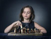 Tonårig flicka som spelar schack Arkivbild