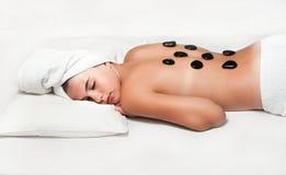 tonårig flicka som tycker om en tillbaka massage med den varma stenen i en brunnsortmitt Arkivfoto