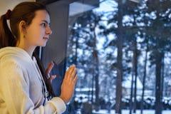 Tonårig flicka som ut ser fönstret med ett vinterlandskap Arkivfoton