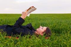 Tonårig flicka som utomhus läser bibeln arkivbild
