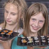 Tonårig flicka två med sushirulle, tonårs- flickor som äter den japanska sushi Arkivfoton