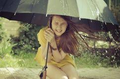 Tonårig flicka under det stora paraplyet i en hällregn Arkivbilder