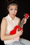 Tonårig flickamodell som spelar en ukulele med ett roligt ansiktsuttryck Royaltyfri Foto