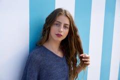 Tonårig flickastående för brunett i vägg för blåa band arkivbild