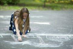 Tonårig flickateckning med krita på trottoaren Utvändigt intresse Arkivbilder