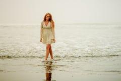 Tonårig flickavandring vid stranden Royaltyfri Bild
