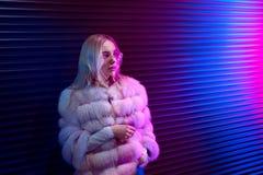 Tonårig hipsterflicka i exponeringsglas som poserar på för bakgrundsgata för neon den purpurfärgade väggen arkivbilder
