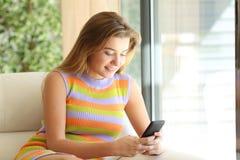 Tonårig kontrollerande smart telefon hemma arkivbilder
