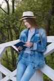Tonårig kvinna läst bok utanför Royaltyfri Foto