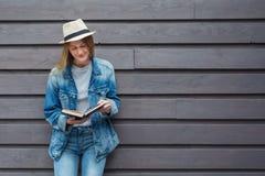 Tonårig kvinna läst bok utanför väggen Royaltyfria Foton