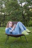 Tonårig kvinna som använder smartphoneyttersidaträdgården Royaltyfri Foto
