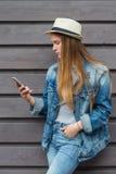 Tonårig kvinnasmartphone utanför den wood väggen Royaltyfria Foton