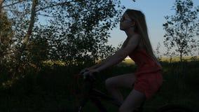 Tonårig kvinnlig med långt hår som cyklar i natur lager videofilmer