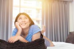 Tonårig lat daghand för flicka på hakan på säng som ser högt tänkande saknat dagdrömma royaltyfri fotografi