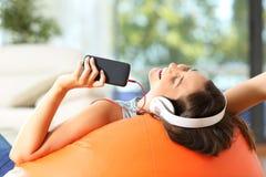 Tonårig lyssnande musik på en puff Arkivbilder