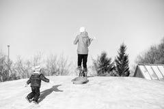 Tonårig och för litet barn sledding Arkivfoton