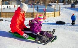Tonårig och för litet barn sledding Fotografering för Bildbyråer