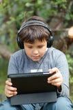 Tonårig pojke i hörlurar med blocket Royaltyfri Foto