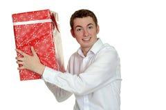 Tonårig pojke med den stora julgåvan Arkivfoton