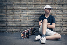 Tonårig pojke med skateboarden som är främst av en tegelstenvägg Arkivbilder