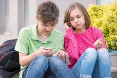 Tonårig pojke och flicka med hörlurar Royaltyfria Foton