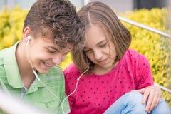 Tonårig pojke och flicka med hörlurar Royaltyfri Fotografi