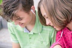 Tonårig pojke och flicka med hörlurar Fotografering för Bildbyråer